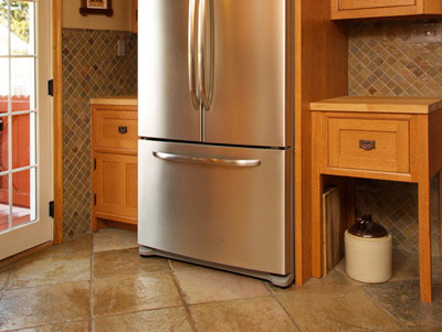 Stainless steel french door refrigerator with bottom freezer, custom oak cabinets, butcher block countertops, slate tile