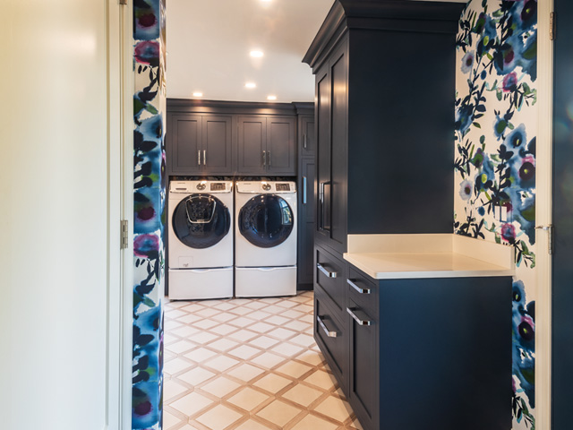 Bold blue laundry cabinetry and watercolor floral wallpaper