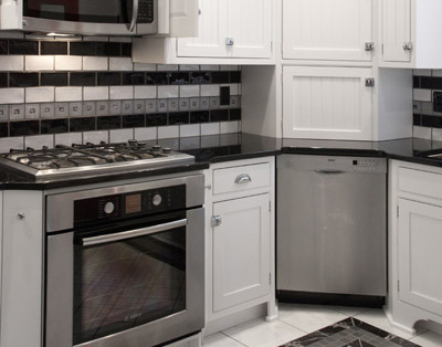 black and white semi-gloss subway tiles, white kitchen cabinets, bead board, inset cabinets, custom tile, crown moulding