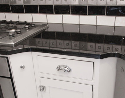 black granite countertops, white cabinets, stainless steel hardware, silver wall tile