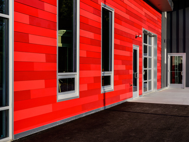 fiber cement siding, red siding, modern design, large windows, angled roof, industrial design, recessed lights, and aluminum trim.