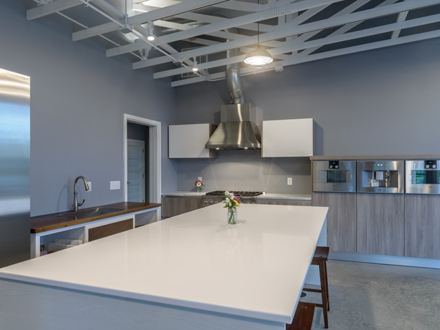 exposed ceilings, modern industrial lighting, burnished concrete floors, modern European kitchen, stainless steel appliances, white quartz counters, and industrial range and hood.
