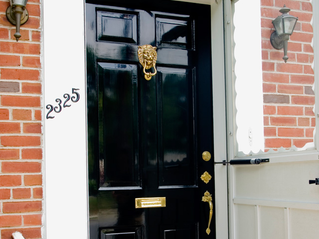 Restored door with high gloss black finish, brass hardware