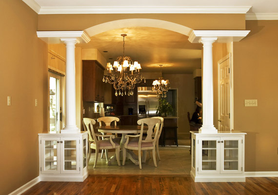 columns, crown moulding, glass doors, custom cabinetry, hardwood floors, archtop ceiling