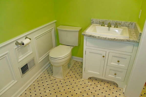 white marble mosaic with black dot accent floor tile, white vanity cabinet, marble countertop, wainscotting, green walls