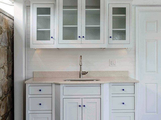 poolhouse wet bar, white exterior cabinets, glass cabinet doors